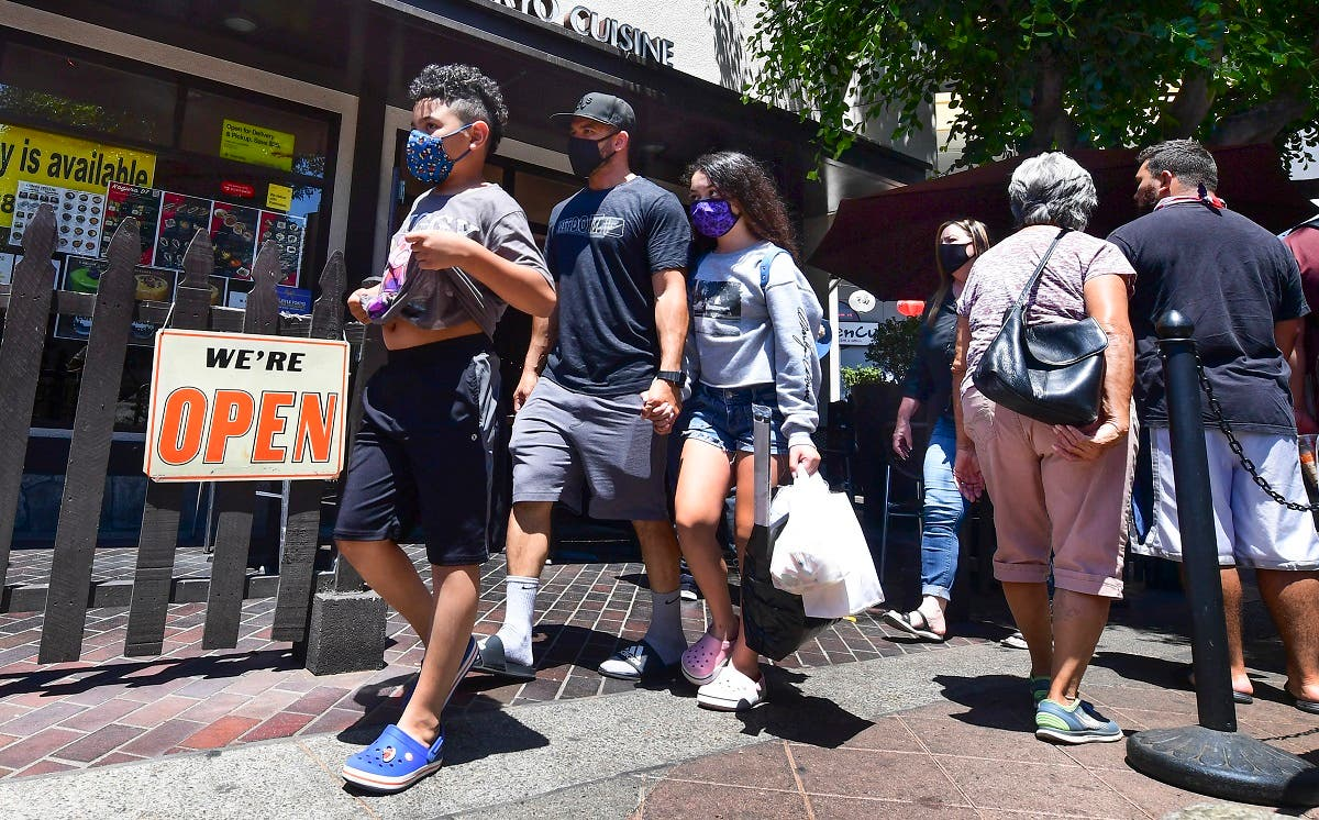Face masks continue to be worn as people walk past restaurants open for business in Los Angeles on June 14, 2021. (Frederic J. Brown/AFP)