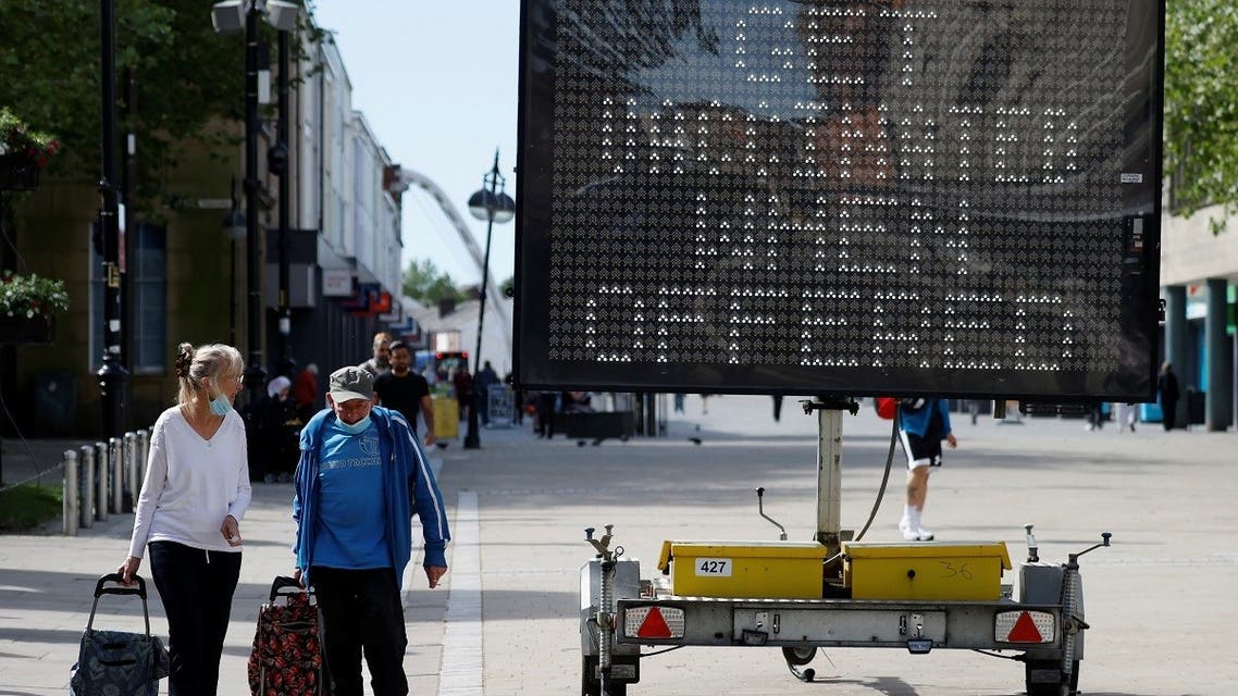 People pull shopping carts as they walk past an information board, amid the outbreak of the coronavirus, in Bolton, Britain, on June 16, 2021. (Reuters)