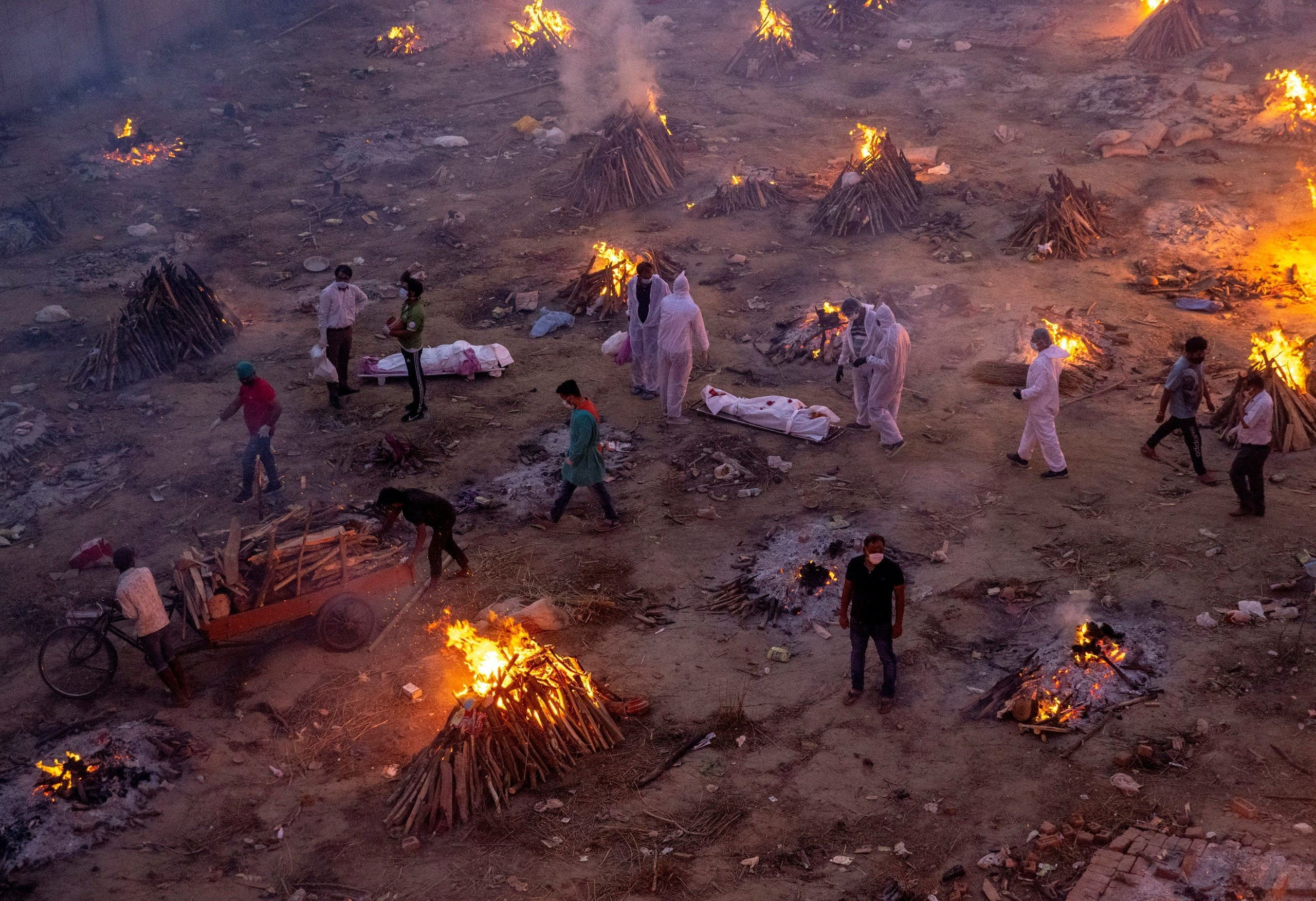 People wait to cremate victims who died due to complications related to the coronavirus disease (COVID-19), at a crematorium ground in New Delhi, India, April 23, 2021. (Reuters)
