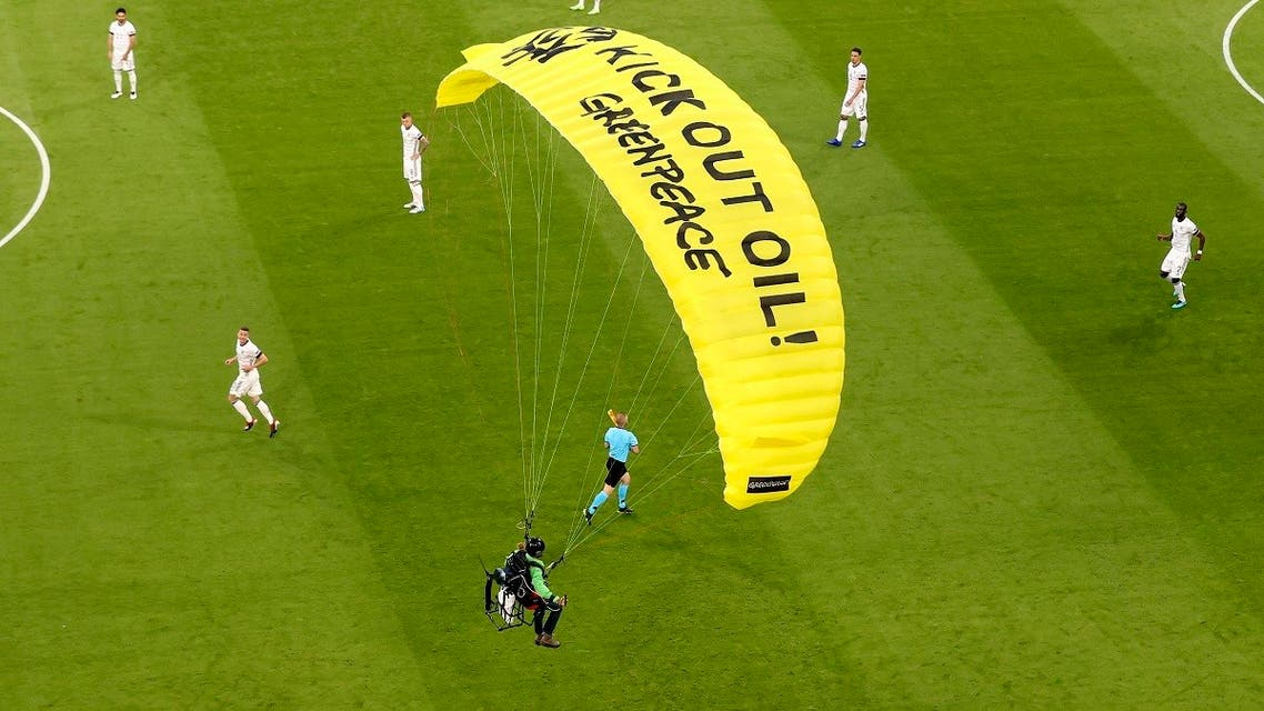 The German players look on as a Greenpeace paraglider lands in the stadium prior to the Euro 2020 soccer championship group F match between France and Germany at the Allianz Arena stadium in Munich, on June 15, 2021. (AP)