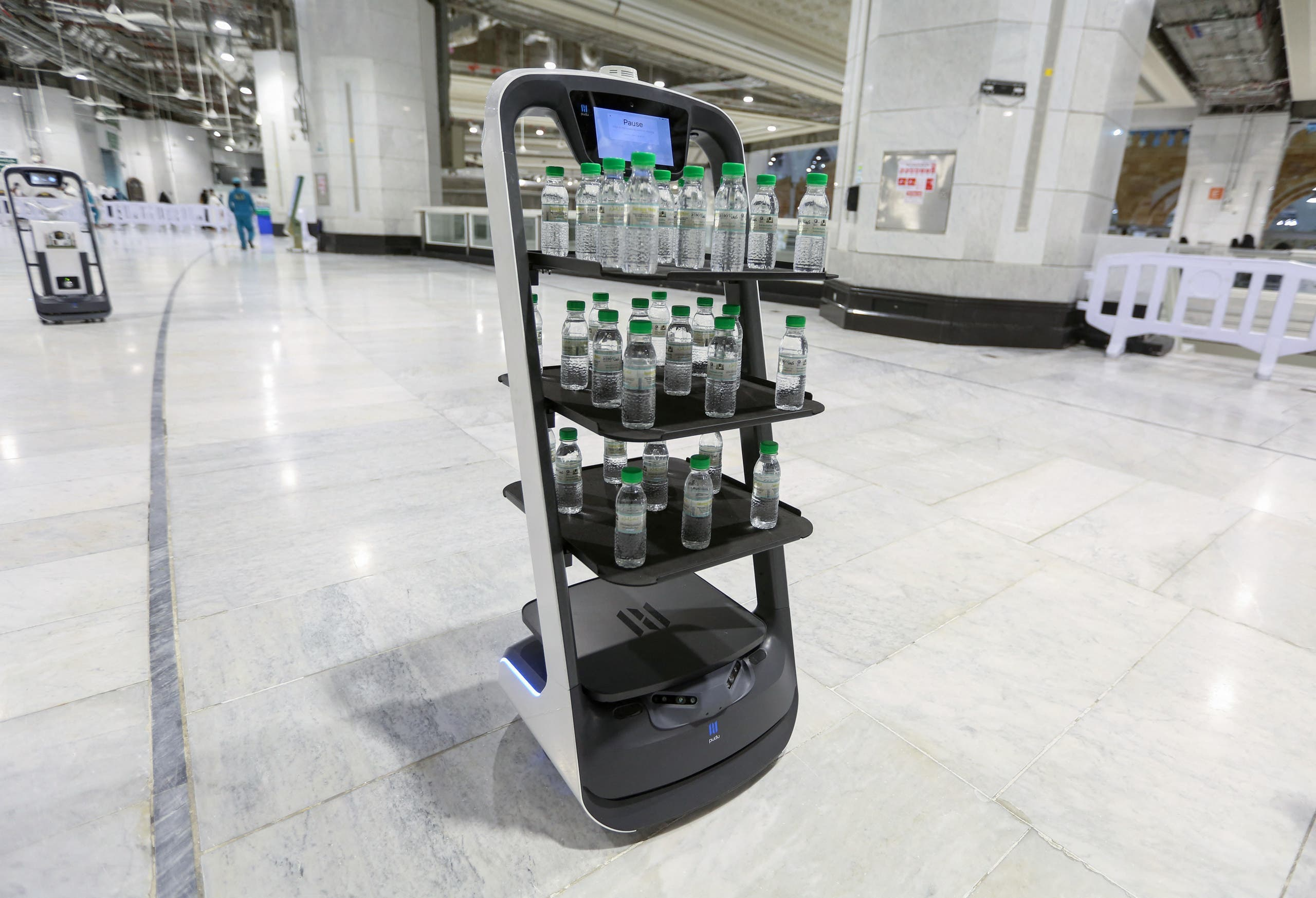 A picture taken on June 15, 2021, shows a smart robot used for the first time at the Grand Mosque in Saudi Arabia's holy city of Mecca, supplying worshippers with bottles of Zamzam water to reduce direct contact with staff as a measure to prevent COVID-19 infections during the yearly hajj pilgrimage. (AFP)
