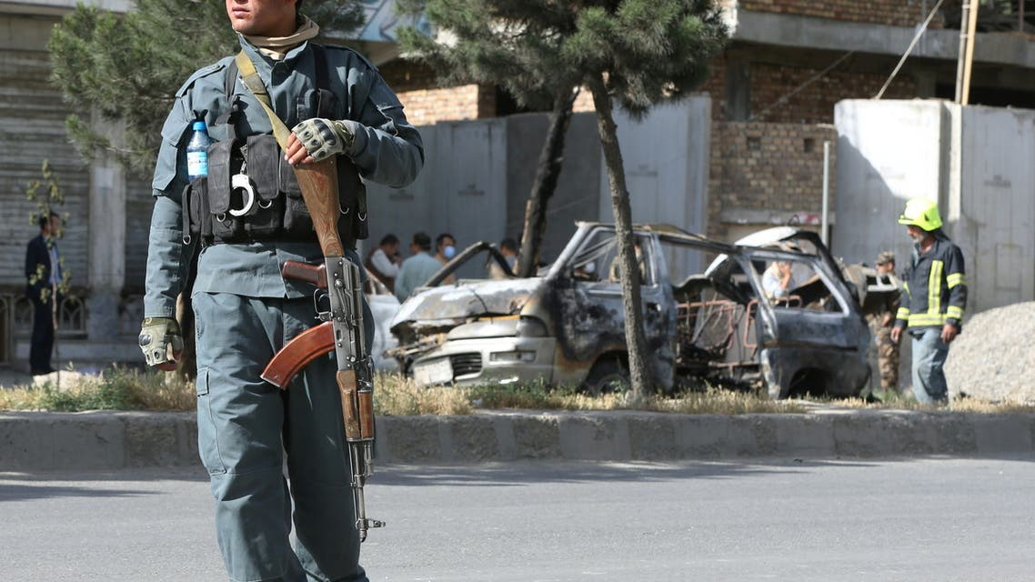 An Afghan police keeps watch while other security forces inspect the wreckage of a passenger van after a blast in Kabul, Afghanistan June 12, 2021. (File photo: Reuters)