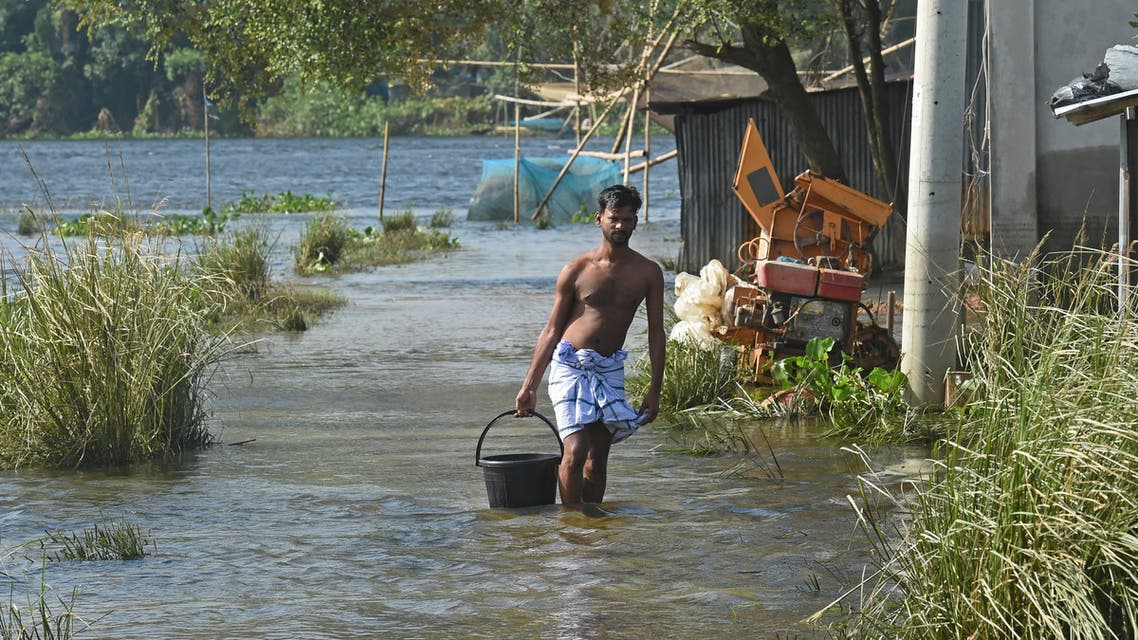 A flood-affected resident makes his way through a flooded village in Savar on August 19, 2020. (AFP)
