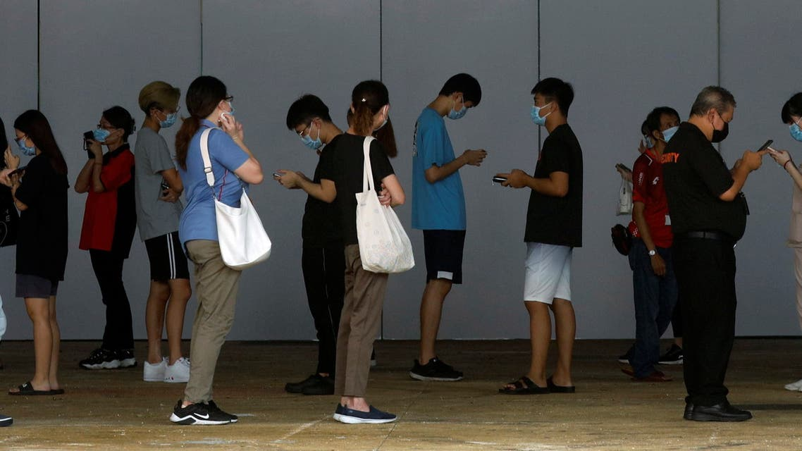 People who had visited a mall which became a coronavirus disease (COVID-19) cluster, queue up for their swab tests in Singapore May 20, 2021. (Reuters)