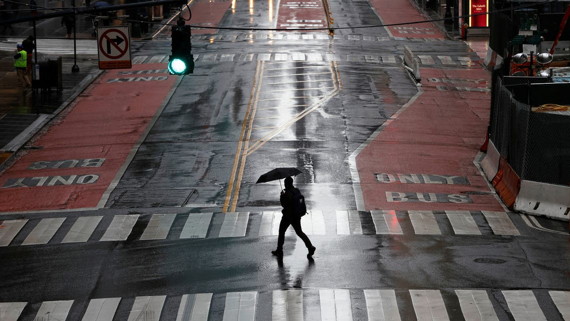 A man carries an umbrella as he walks across an empty East 42nd Street in midtown Manhattan as the coronavirus disease (COVID-19) outbreak continues, in New York City, New York, US, March 23, 2020. (Reuters)