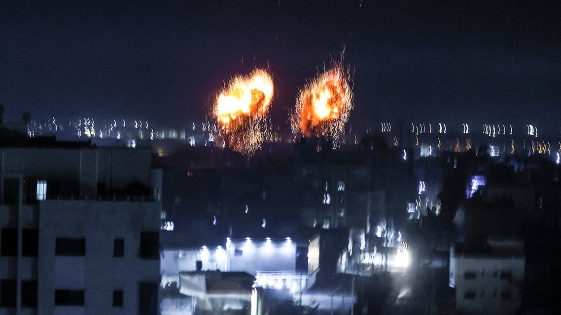 Explosions light-up the night sky above buildings in Gaza City as Israeli forces shell the Palestinian enclave, early on June 16, 2021. (AFP)