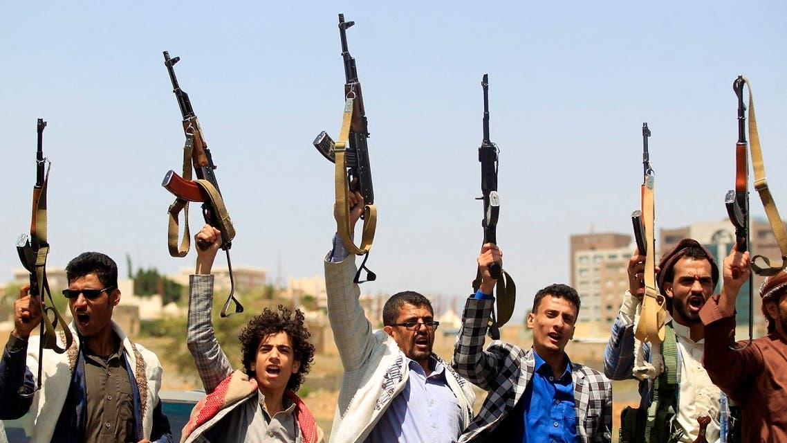 Yemeni fighters loyal to the Iran-backed Houthis raise their weapons during a rally in the capital Sanaa, on May 20, 2021. (AFP)