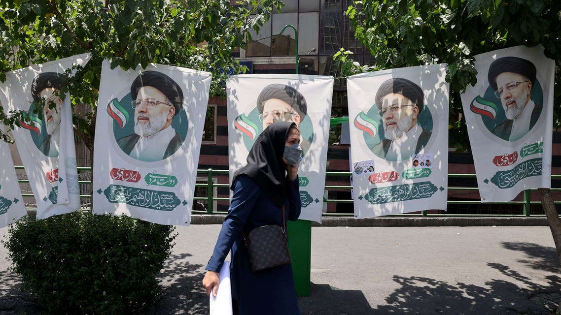 An Iranian woman walks past banners of ultraconservative cleric and presidential candidate Ebrahim Raisi, in Tehran, on June 17, 2021, on the eve of the Islamic republic's presidential election. Iranians will vote for a new president on June 18, with seven candidates in the race. People will also elect municipal councils, while six candidates will also be chosen to join the Assembly of Experts which names, oversees and can dismiss the supreme leader.