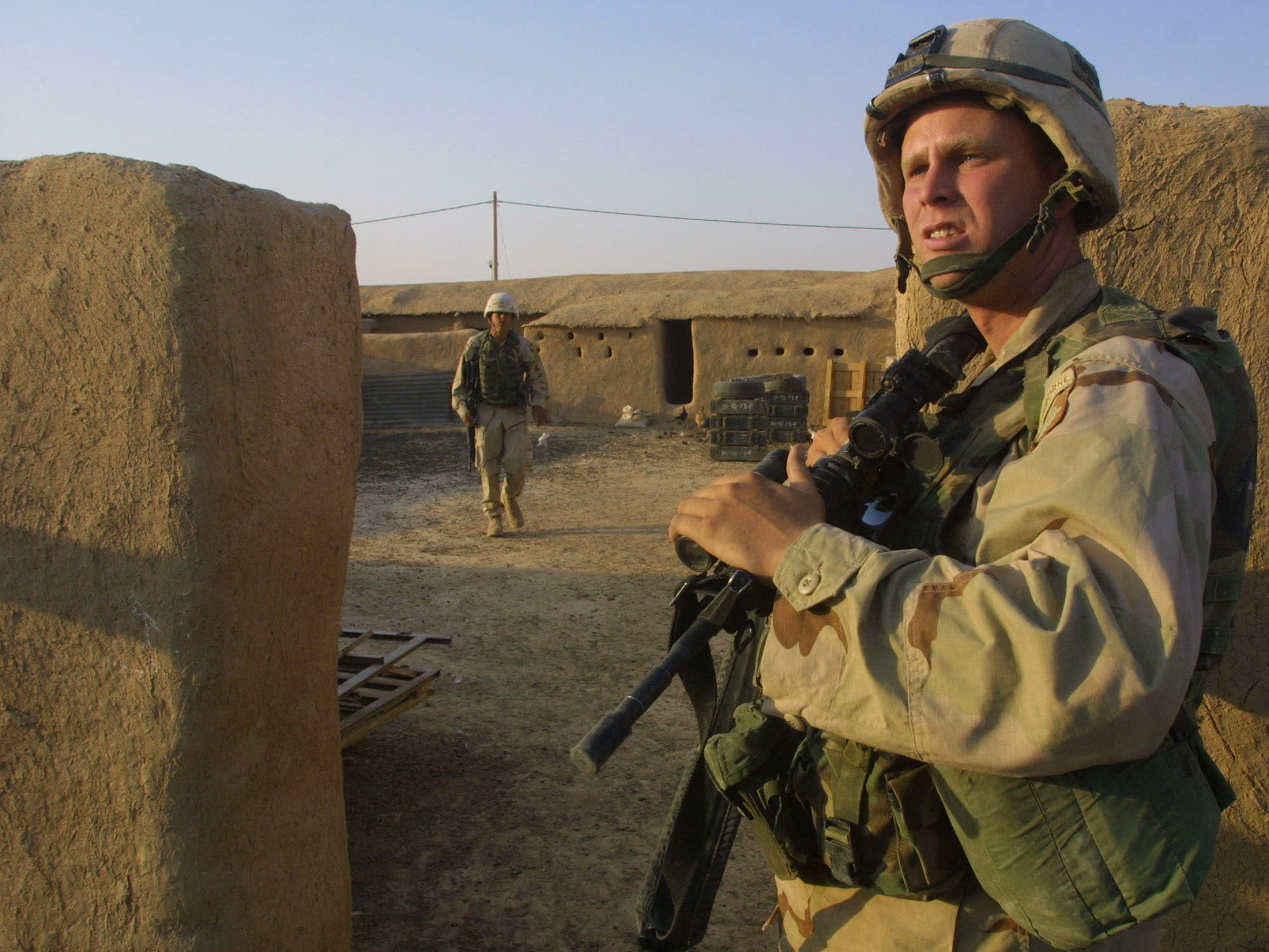A US soldier from the 101st Airborne Division, Alpha company, guards the entrance of a house in the village of Alaiba, 70 kms southwest of the northern Iraqi city of Mosul, as others search it 01 October 2003. The soldiers confiscated a large quantity of weapons, including a canon, several mortars, and kalashnikovs in the village. Depressed by months of service in Iraq and under stress from daily attacks, many of the troops of the US 101st Airborne Division apparently now have only one dream: to go home. Officially 10 soldiers have been killed and 122 wounded in the province since they were deployed here on April 22. (AFP)
