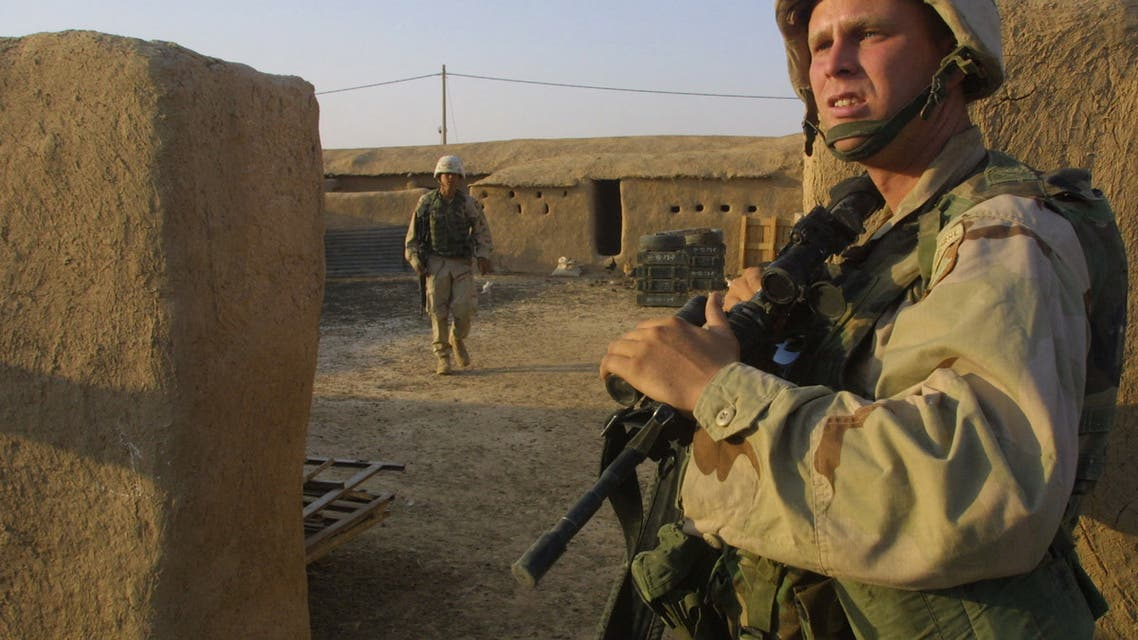 A US soldier from the 101st Airborne Division, Alpha company, guards the entrance of a house in the village of Alaiba, 70 kms southwest of the northern Iraqi city of Mosul, as others search it 01 October 2003. The soldiers confiscated a large quantity of weapons, including a canon, several mortars, and kalashnikovs in the village. Depressed by months of service in Iraq and under stress from daily attacks, many of the troops of the US 101st Airborne Division apparently now have only one dream: to go home. Officially 10 soldiers have been killed and 122 wounded in the province since they were deployed here on April 22. AFP PHOTO/Ahmad AL-RUBAYE