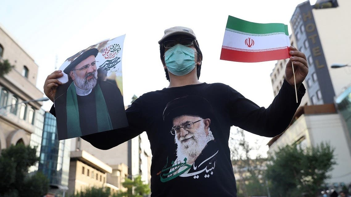 A supporter of presidential candidate Ebrahim Raisi holds a posters of him during an election rally in Tehran, Iran. (Reuters)