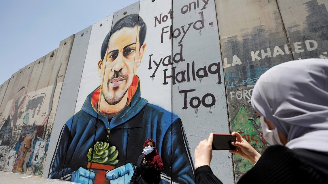A Palestinian woman takes pictures of her friend posing in front of the Israeli barrier with a mural depicting Iyad al-Halaq, an unarmed and autistic Palestinian who was shot dead by Israeli police, in Bethlehem in the Israeli-occupied West Bank on June 18, 2020. (Reuters)