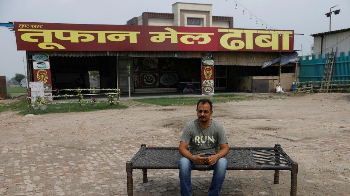 Vikas Malik, owner of a dhaba, a small restaurant, sits for a picture in front of his temporarily closed dhaba along a national highway in Murthal, in the northern state of Haryana, India, on June 17, 2021. (Reuters)