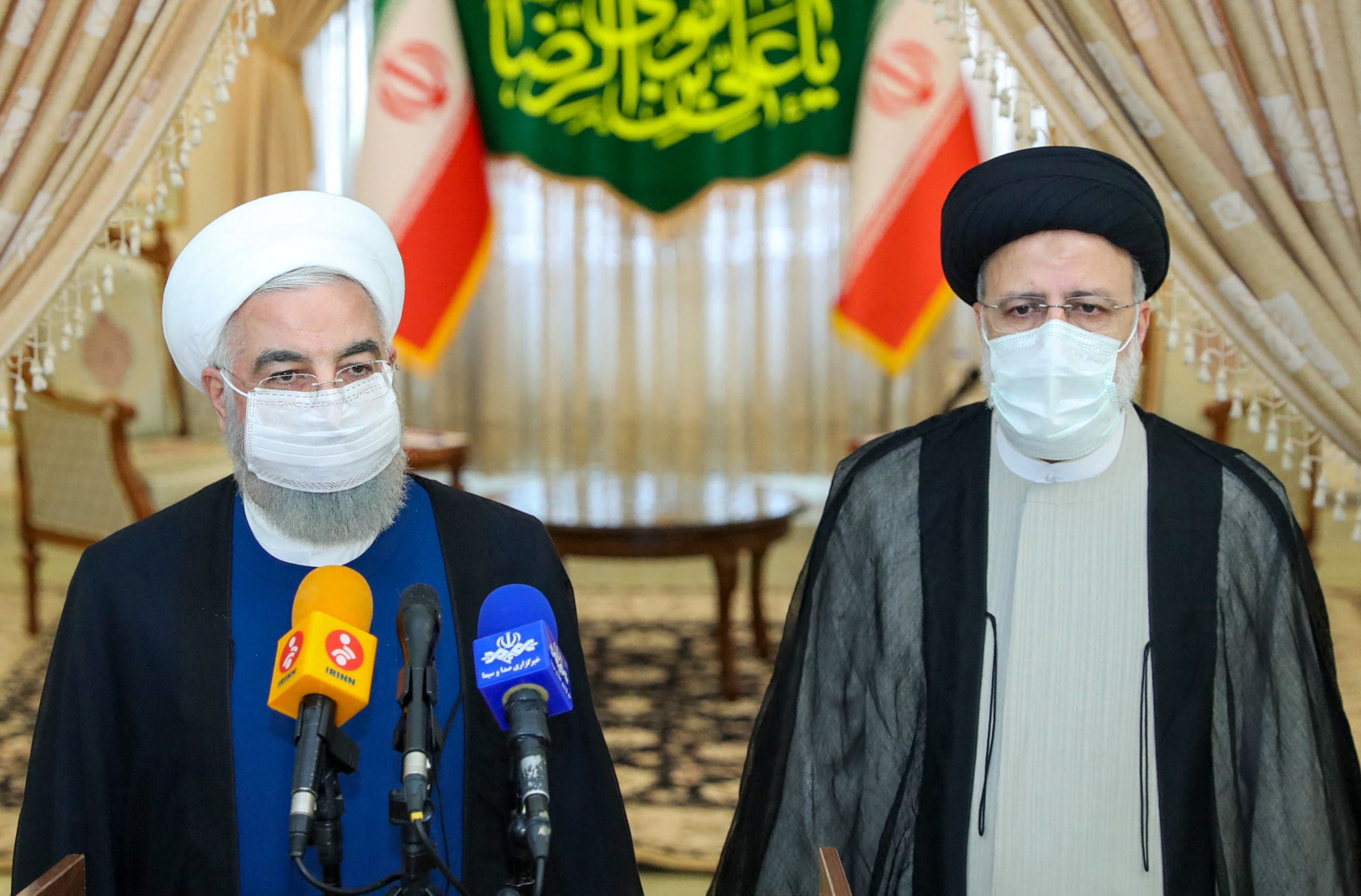 A handout picture provided by the Iranian presidency on June 19, 2021, shows outgoing President Hassan Rouhani (L) taking in part in a press conference with President-elect Ebrahim Raisi (R) during his visit to congratulate the ultraconservative cleric on winning the presidential election. (Reuters)
