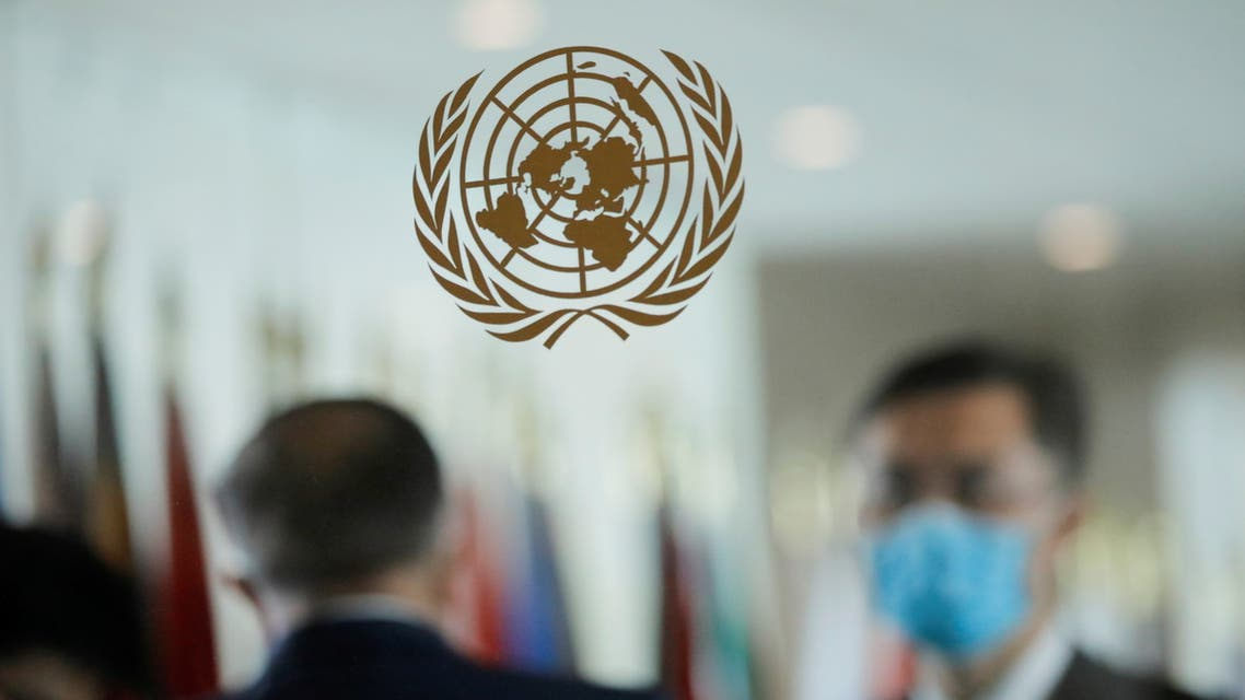 People wearing face masks are seen behind the emblem of the United Nations at its headquarters. (File Photo: Reuters)