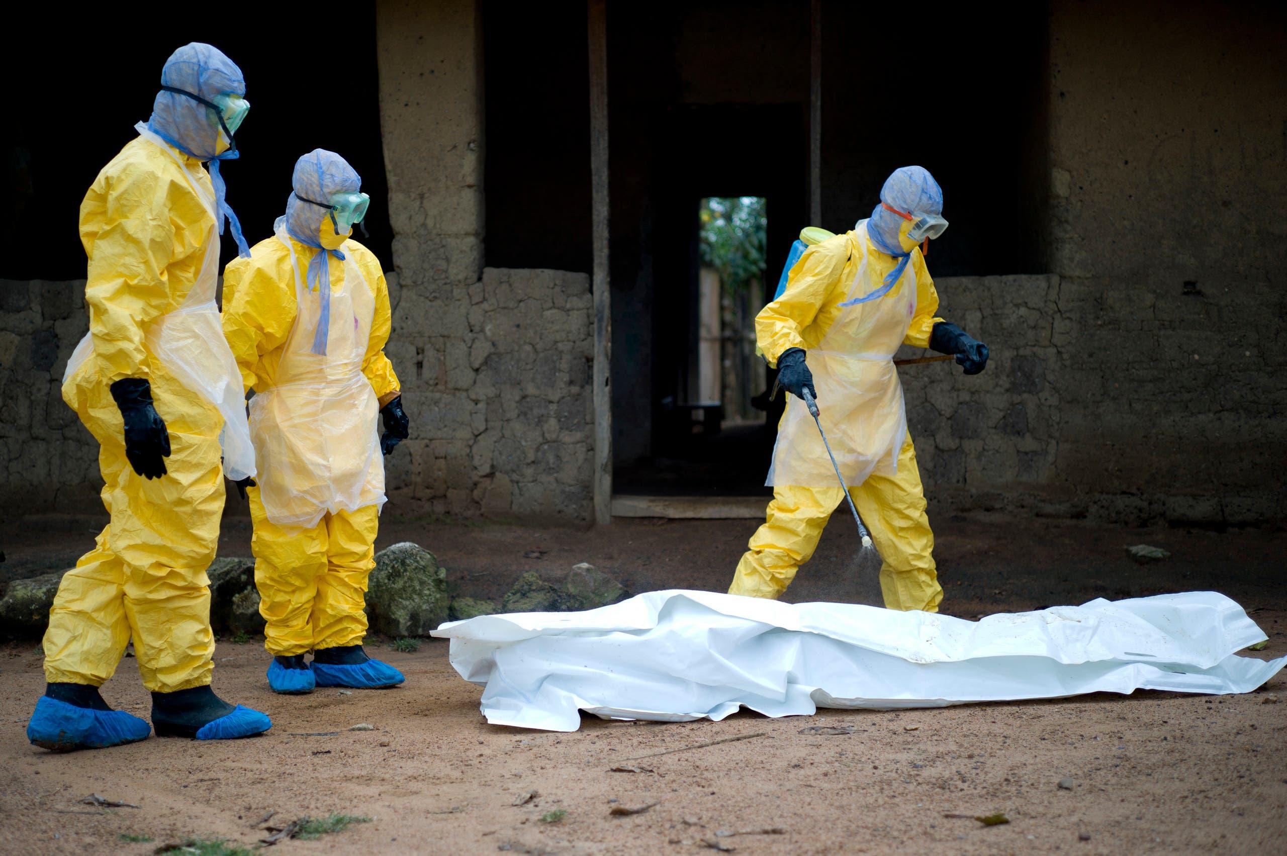 عمال صحيون ينقلون جثة متوفى بإيبولا في غينيا في 2014 (أرشيفية)