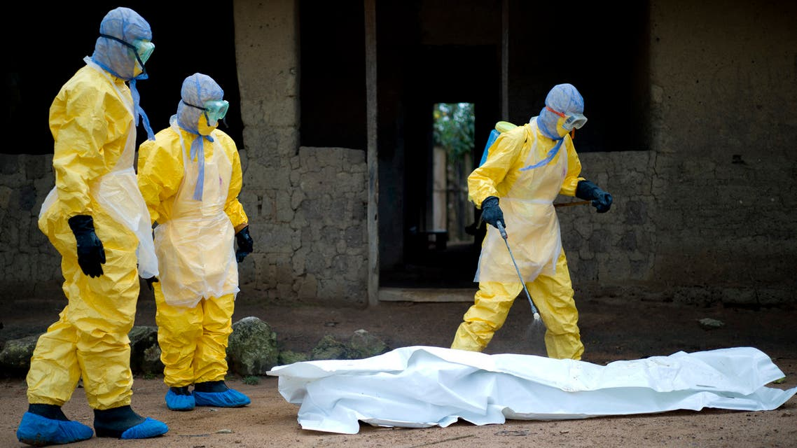 (FILES) In this file photo taken on November 19, 2014 Health workers from Guinea's Red Cross prepare to carry the body of a victim of the Ebola virus in Momo Kanedou in Guinea . The World Health Organization on June 19, 2021 officially announced the end of Guinea's second Ebola outbreak which was declared on February 14. AFP