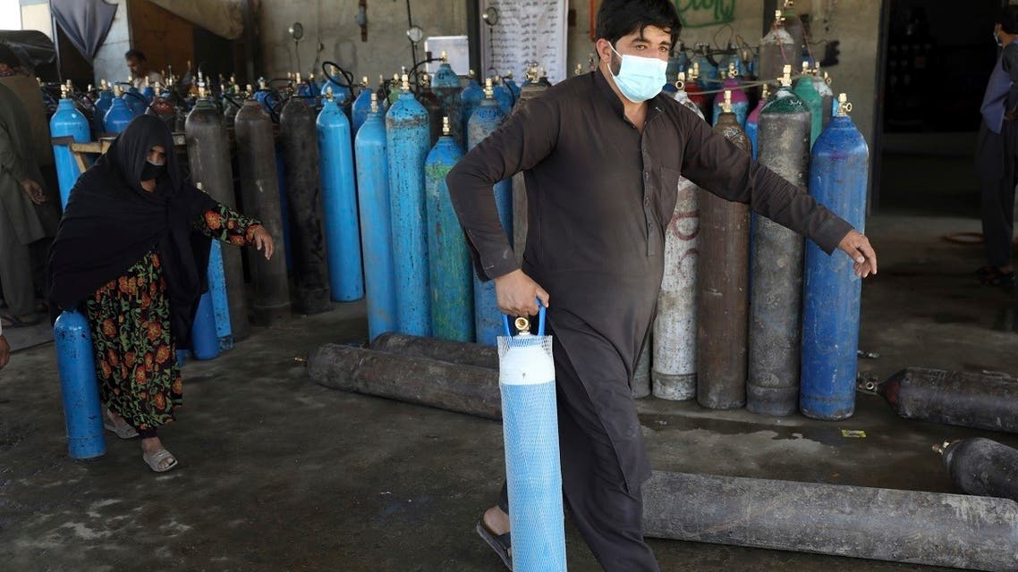 A man and woman carry an oxygen cylinders from a privately owned oxygen factory, in Kabul, Afghanistan, Saturday, June 19, 2021. (AP/Rahmat Gul)