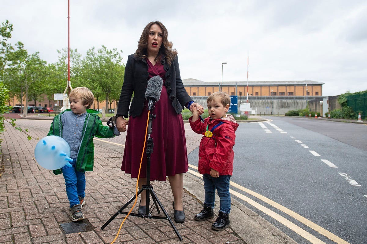 Stella Moris stands with her children Gabriel, four, left, and Max, two, as she speaks to the media, outside Belmarsh Prison, following a visit to her partner and their father Julian Assange in London, Saturday June 19, 2021. (Dominic Lipinski/PA via AP)