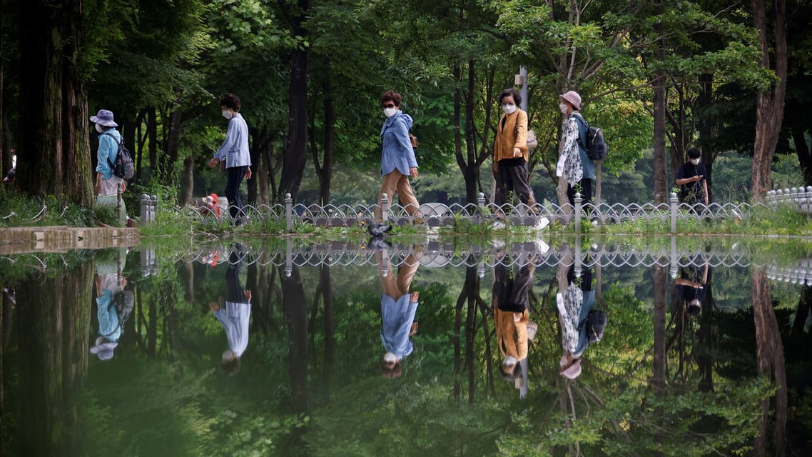 Women wearing masks to avoid contracting the coronavirus disease (COVID-19) take a walk at a park in Seoul, South Korea, June 1, 2021. (Reuters)