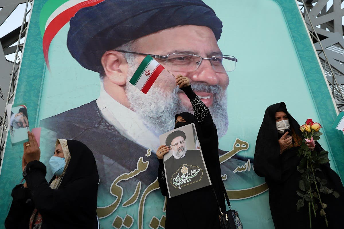 A supporter of Ebrahim Raisi displays his portrait during a celebratory rally for his presidential election victory in Tehran, Iran June 19, 2021. (Majid Asgaripour/WANA (West Asia News Agency) via Reuters)