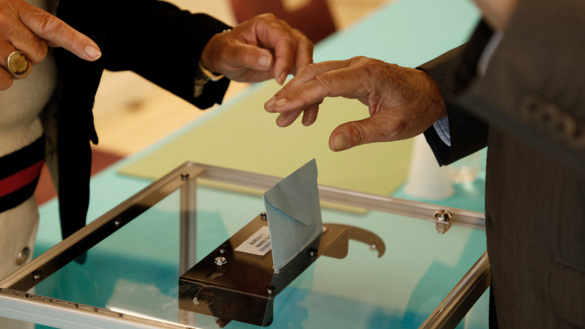 A voter casts his ballot at a polling station in Cucq, Northern France, for the first round of the French regional elections on June 20, 2021. (AFP)