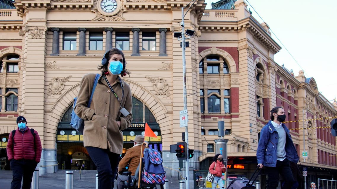 Pedestrians cross the road at Flinders Street Station on the first day of eased coronavirus disease (COVID-19) restrictions for the state of Victoria following an extended lockdown in Melbourne, Australia, June 11, 2021. (Reuters)
