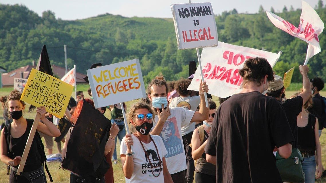 People take part in a protest against the violent pushbacks of migrants, allegedly conducted by Croatian police, near the border crossing between Croatia and Bosnia Herzegovina in Maljevac, Croatia, Saturday, June 19, 2021. (AP/Edo Zulic)