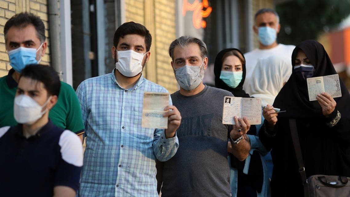 Voters hold their documents while in line at a polling station during the presidential election in Tehran, Iran June 18, 2021. (Majid Asgaripour/WANA (West Asia News Agency) via Reuters)