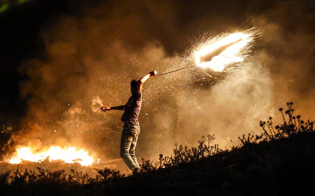 متظاهر فلسطيني يلقي قذيفة مشتعلة على الحدود مع إسرائيل - أرشيفية