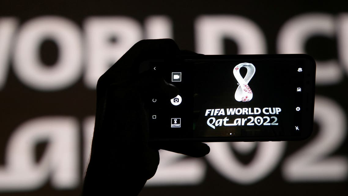A man takes a picture of the tournament's official logo for the 2022 Qatar World Cup as displayed on the wall of amphitheater, in Doha, Qatar, September 3, 2019. (Reuters)