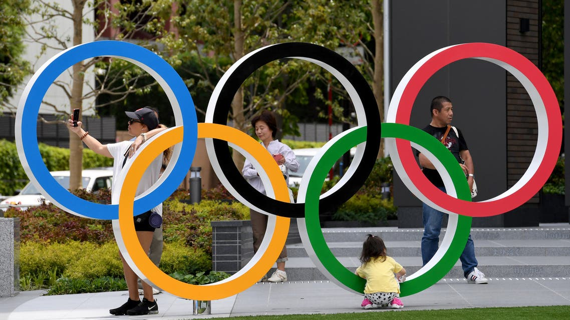 People takes photographs of the Olympic Ring at the Japan Sport Olympic Square beside the under constructing national stadium in Tokyo on May 18, 2019. (File photo: AFP)
