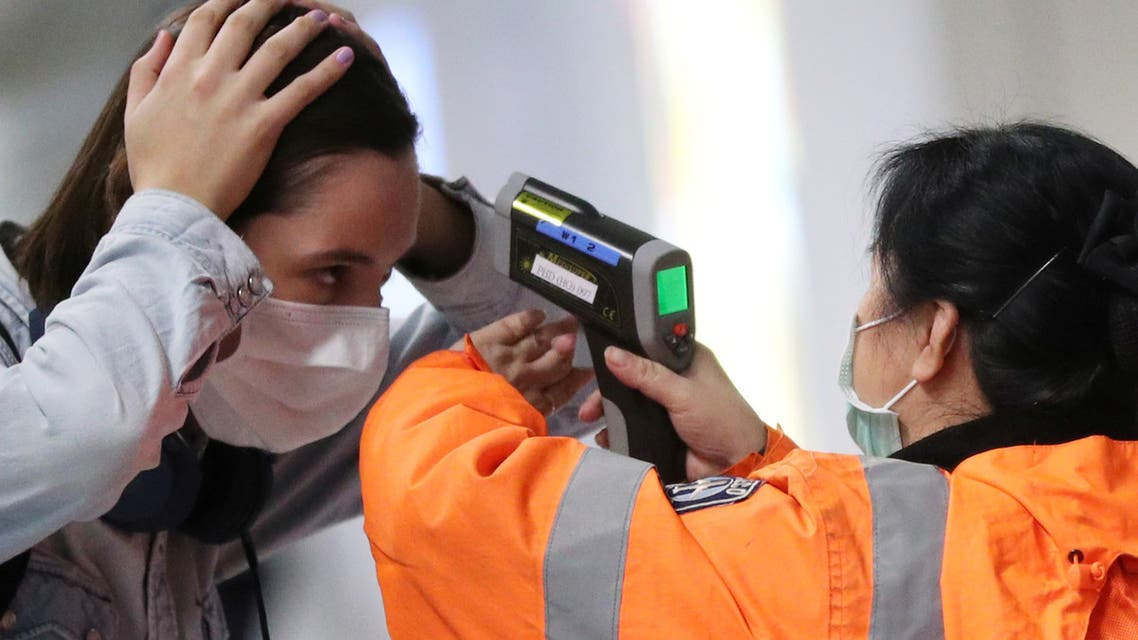A worker checks the temperature of a passenger arriving into Hong Kong International Airport with an infrared thermometer, following the coronavirus outbreak in Hong Kong, China, February 7, 2020. REUTERS/Hannah McKay