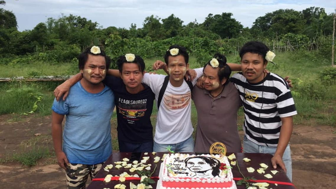 Men with flowers in their hair in support of Myanmar's detained leader, Aung San Suu Kyi, pose next to the cake with frosting imprint of her face to mark her birthday, in Myanmar, June 19, 2021. (Reuters)