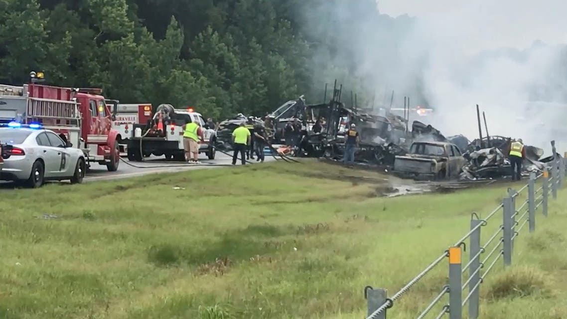 Emergency personnel work at the accident site as smoke rises from the wreckage after about 18 vehicles slammed together on a rain-drenched Alabama highway during Tropical Storm Claudette, in Butler County, Alabama, US, June 19, 2021. (Reuters)