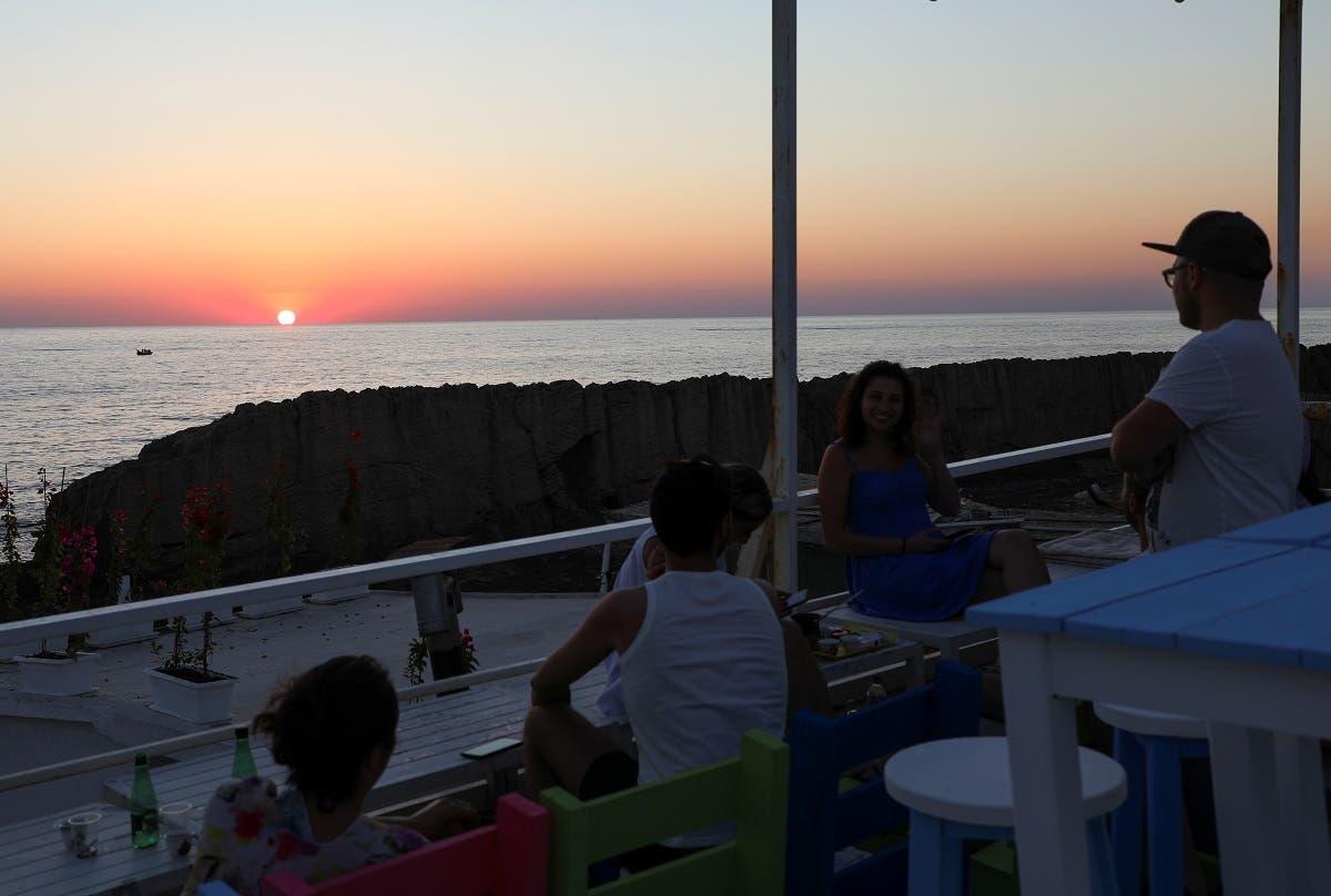 People sit at a restaurant during sunset in Batroun, Lebanon June 5, 2021. (Reuters/Mohamed Azakir)