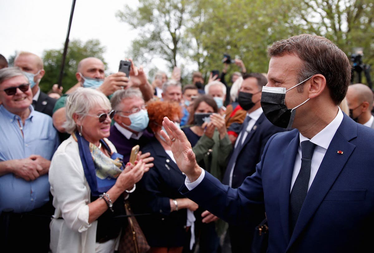 French President Emmanuel Macron (R), wearing a mask, greets voters at the polling station in Le Touquet, during the first round of the French regional elections on June 20, 2021. (AFP)