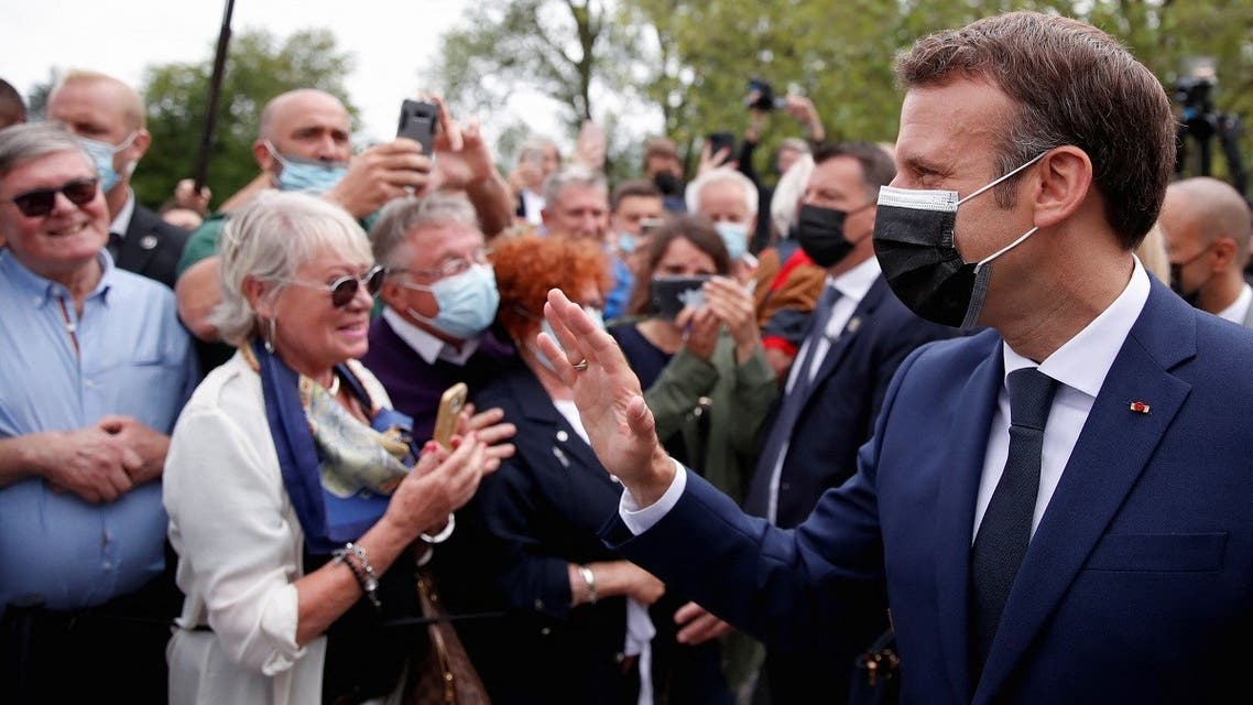 French President Emmanuel Macron (R), wearing a mask, greets voters at the polling station in Le Touquet, during the first round of the French regional elections on June 20, 2021. (Christian Hartmann/Pool/AFP)
