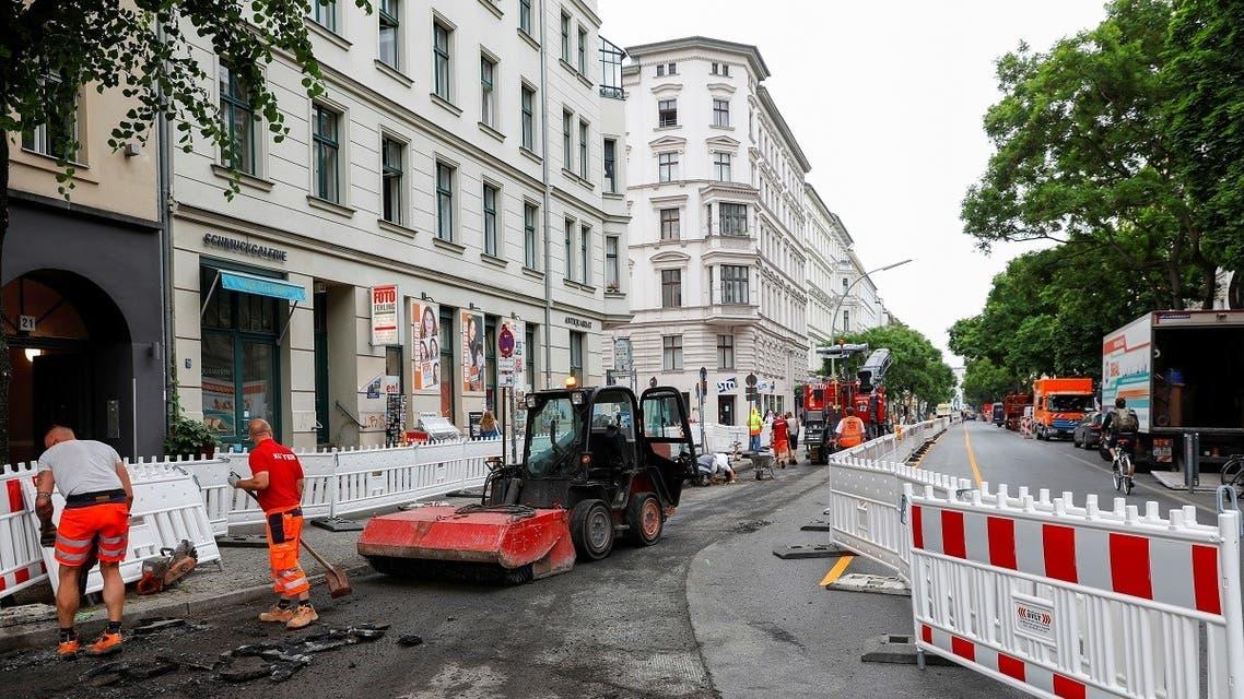 Workers build bicycle lanes in Bergmannstrasse in Berlin, Germany, on June 22, 2021. (Reuters)