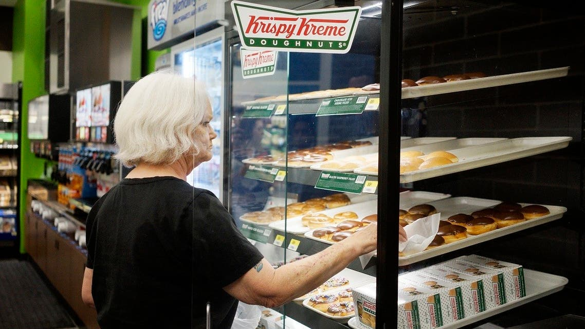 A customer buys Krispy Kreme doughnuts at a Walmart to Go convenience store which is open on a trial basis in Bentonville, Arkansas, US. (Reuters)