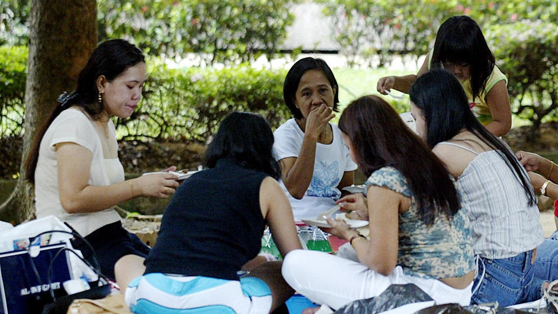 Domestic helpers enjoy a picnic in the shade at Gulung-gulung park in Singapore, 27 July 2003. Singapore's tough campaign to curb employer abuses against foreign maids has improved their working conditions, but civic activists are calling for more reforms saying various forms of indignities persist. (File photo: AFP)