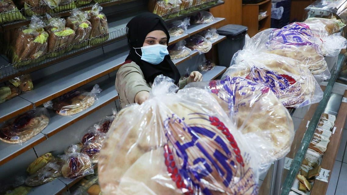 A vendor wearing a face mask arranges bread for sale inside a bakery in Beirut, Lebanon December 7, 2020. (Reuters)