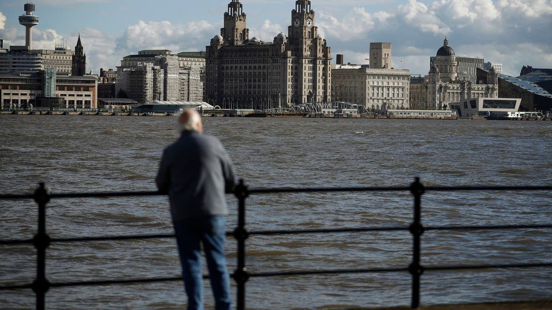 A man looks towards Liverpool's iconic waterfront property the Royal Liver building (C) across the River Mersey in Birkenhead , northern England October 17 , 2016. The 105 year old building is to be sold for the first time, for an expected 40 million pounds ($50 million). (Reuters)