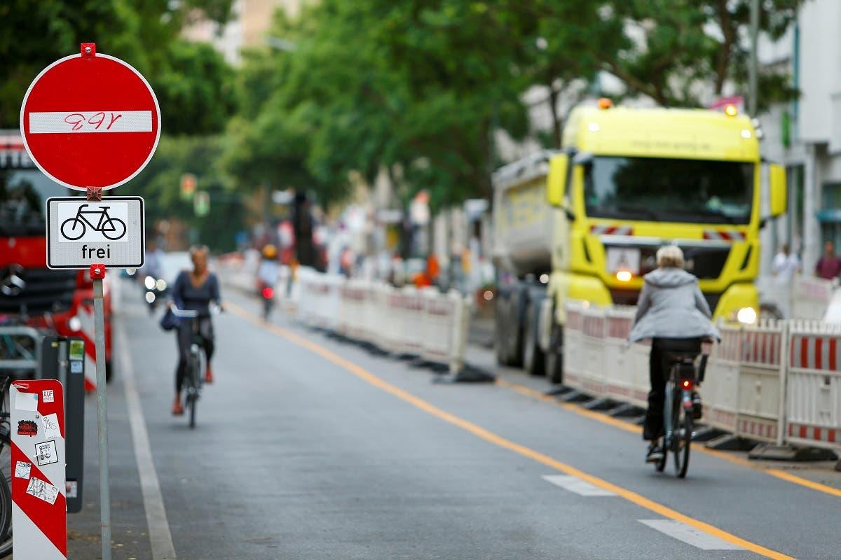 People ride on bicycles as workers build bicycle lanes in the Bergmannstrasse in Berlin, Germany, on June 22, 2021. (Reuters)