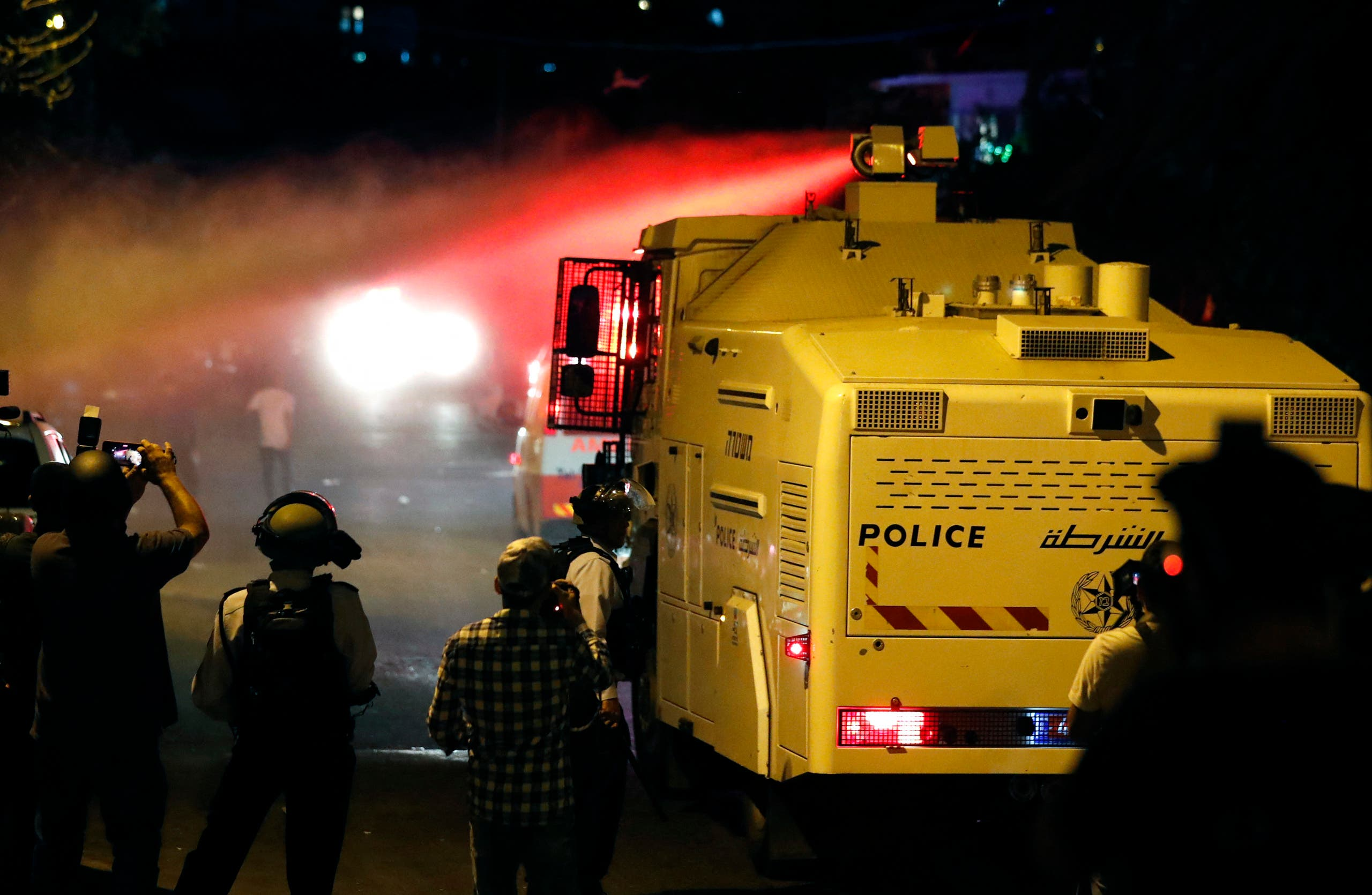Israeli security forces spray Palestinians with skunk water in the east Jerusalem neighbourhood of Sheikh Jarrah on June 21, 2021. (AFP)