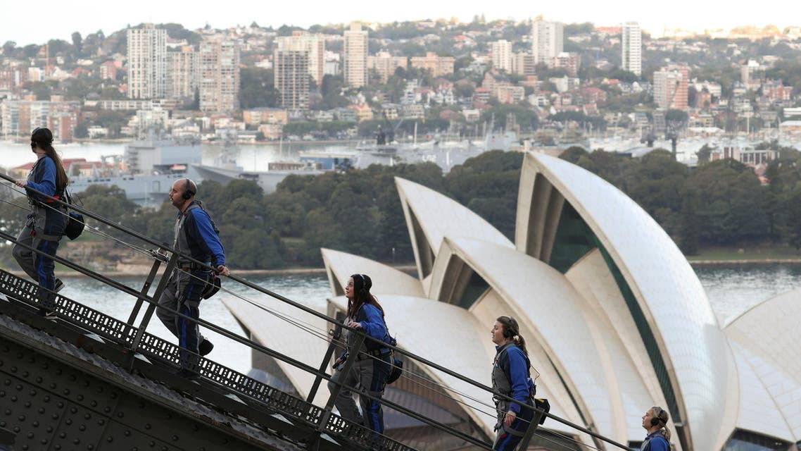People climb the Sydney Harbour Bridge above the Sydney Opera House on a guided excursion in Sydney. (Reuters)