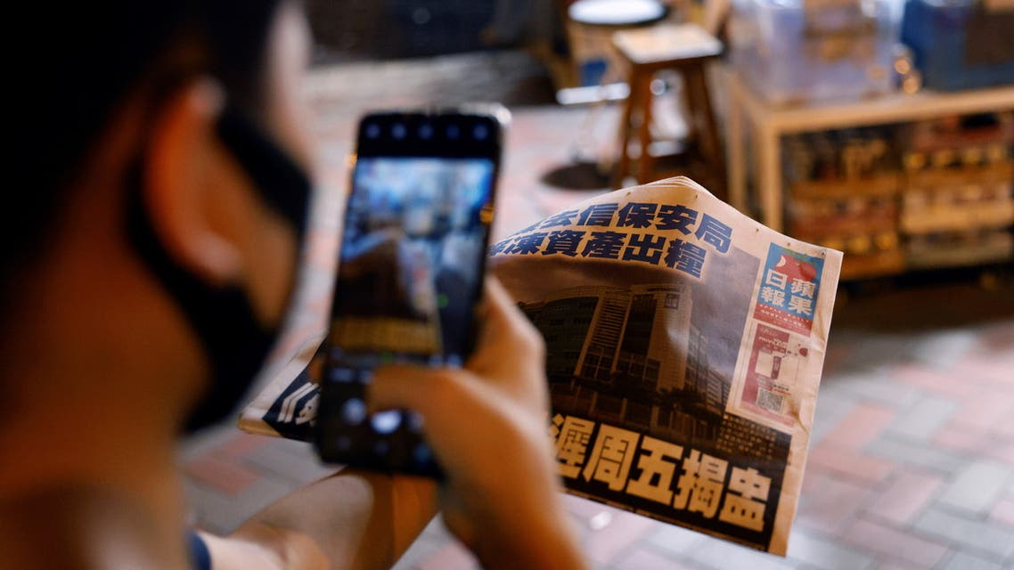 A man takes a photo of his copy of the Apple Daily newspaper after it looked set to close for good by Saturday following police raids and the arrest of executives in Hong Kong, China June 22, 2021. (Reuters)