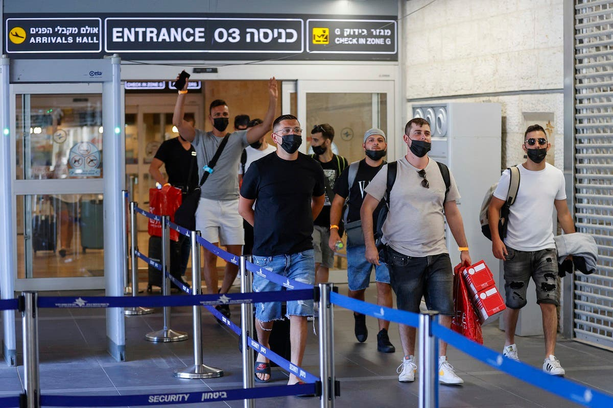 Vaccinated tourists wearing masks for COVID-19 protection arrive to Israel's Ben Gurion Airport near Tel Aviv on May 23, 2021, after a partial re-opening of the border to inoculated tourists from 14 countries. (AFP)