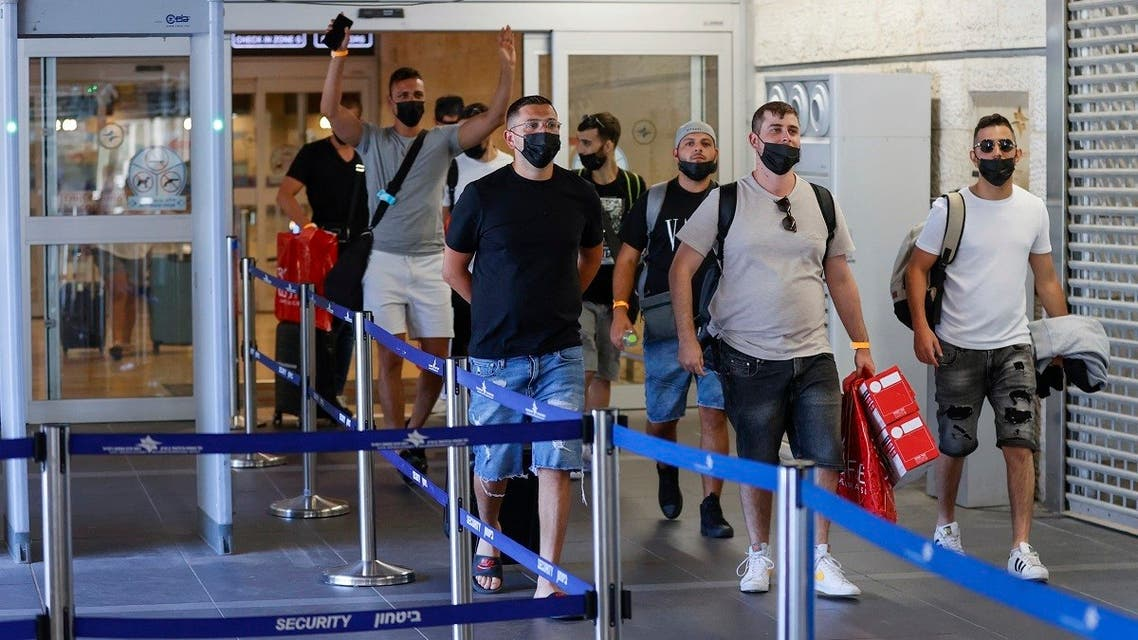 Vaccinated tourists wearing masks for COVID-19 protection arrive to Israel's Ben Gurion Airport near Tel Aviv on May 23, 2021, after a partial re-opening of the border to inoculated tourists from 14 countries. (Jack Guez/AFP)