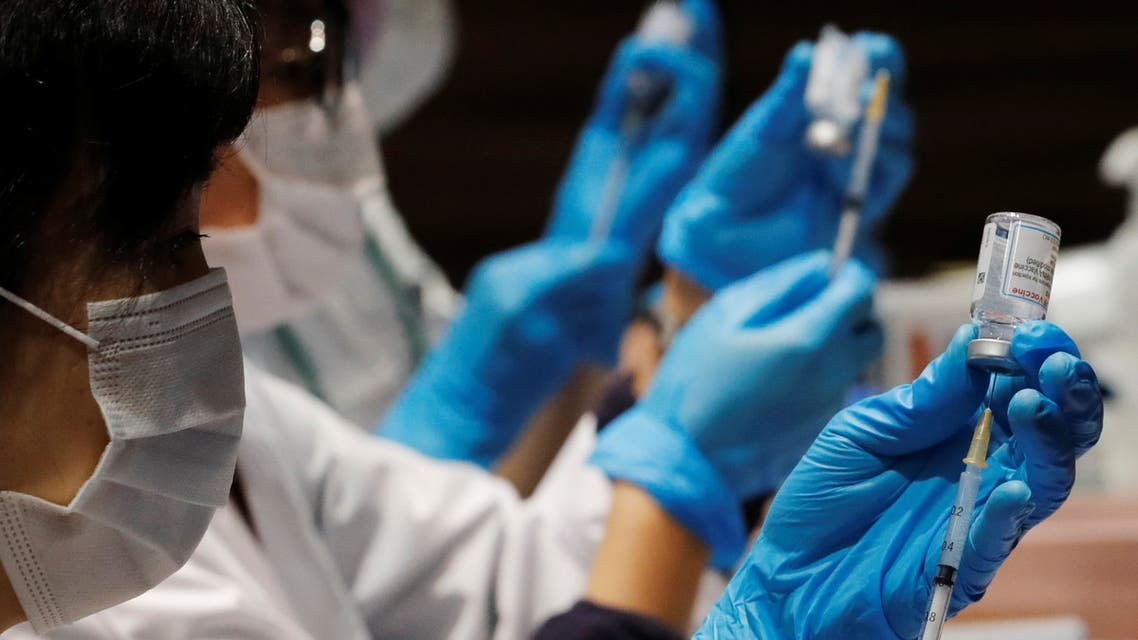 Healthcare workers prepare doses of the Moderna coronavirus disease (COVID-19) vaccine before administering them to staffers of Japan's supermarket group Aeon at the company's shopping mall in Chiba, Japan June 21, 2021. (Reuters)
